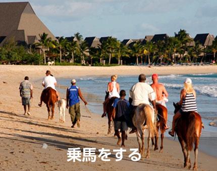 浜辺で乗馬をする